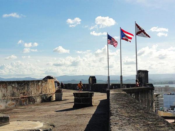 Tres banderas ondean en el Fuerte de San Cristóbal, en San Juan: la de Estados Unidos, la del Estado asociado de Puerto Rico y la Cruz de Borgoña, símbolo esta última de los tres siglos de época virreinal en que Puerto Rico estuvo unido políticamente al resto de Hispanoamérica, bajo la Corona española.